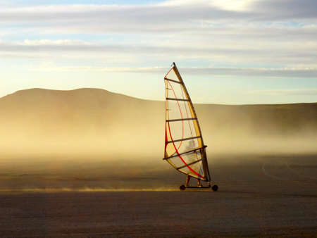 A land wind surfer on a dusty remote dry lake bed.