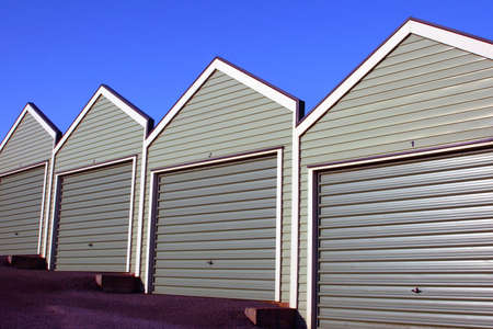 A row of uniform garages with roller doors on a blue sky background.
