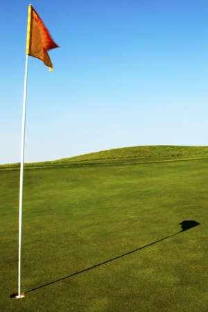 A pristine golf green and flag in the morning. Stock Photo