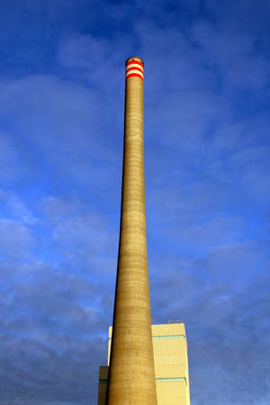 An industrial chimney stack on a blue cloud background.