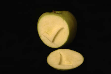 A tick symbol carved into an apple on a black background. Stock Photo