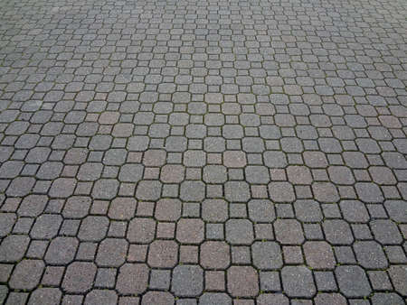 A uniformly patterned brick paving textured background.