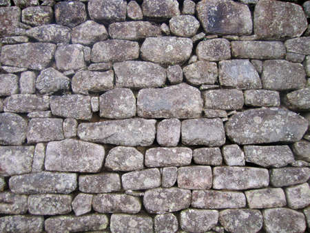 A weathered ancient stone wall background with texture.                      Stock Photo