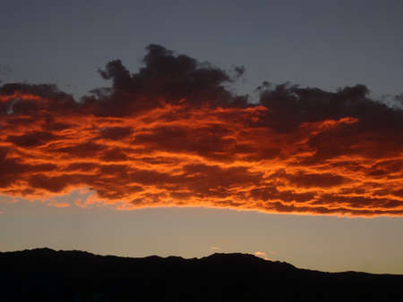 An vivid orange cloud band above a mountain range.