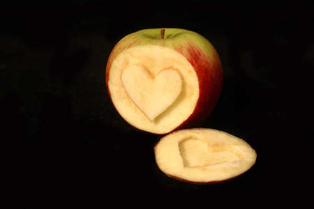 A heart symbol carved into an apple on a black background.
