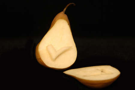 A tick symbol carved into a pear on a black background.