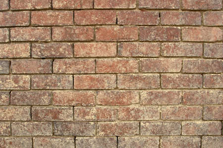 A weathered red brick wall textured background. Stock Photo