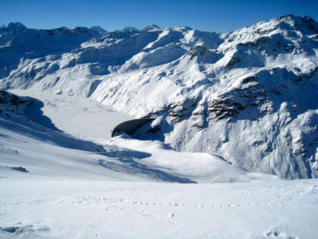 A dam wall and frozen lake in the alps of southern switzerland