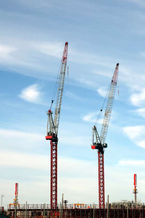 Two large red and white construction cranes on a cloudy sky background  Stock Photo