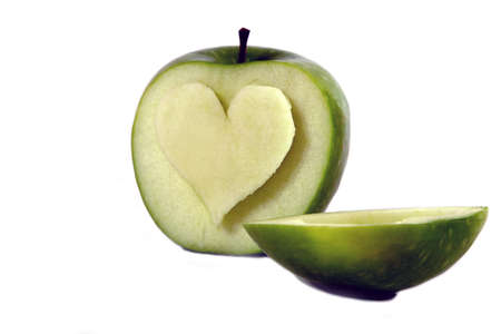 A heart symbol carved into an apple on a white background