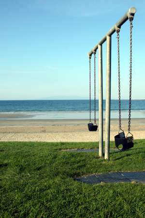 A set of swings next to a beach in New Zealand
