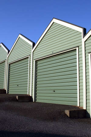 A group of modern garages with car doors on a blue sky background