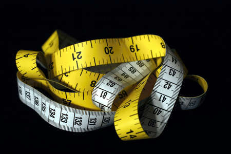 Imperial and Metric measuring tape on a black background  Stock Photo