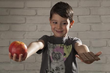 alergy: child chooses chocolate or apple Stock Photo