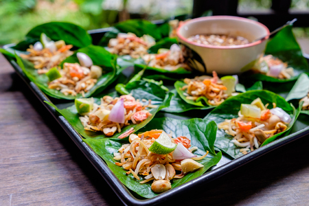 thai dessert: Thai appetizer called Miang Kham, some of nutritious snack wrapped in leaves with a sweet and salty sauce. Stock Photo