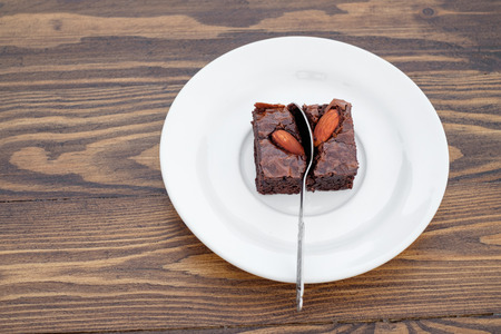 heart white: Homemade chocolate almond brownie were divided with a spoon in white dish on wood table.