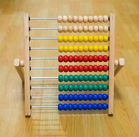 blue background: Colorful abacus toy for kids on wooden floor.