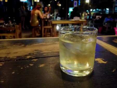 manlike: Glass of whiskey and ice cubes on wooden table with nightlife background.