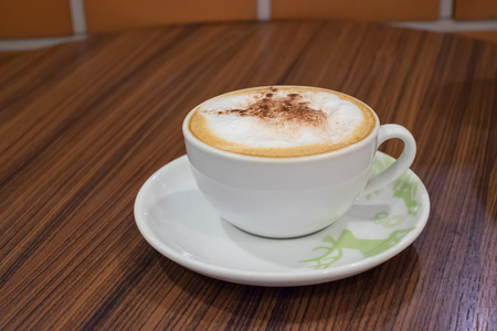 cappuccino cup: White cup containing hot cappuccino coffee on wooden table in cafe.