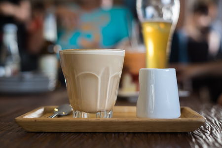 the daily grind: A glass of hot Piccolo latte coffee in wood tray on wooden table in cafe.