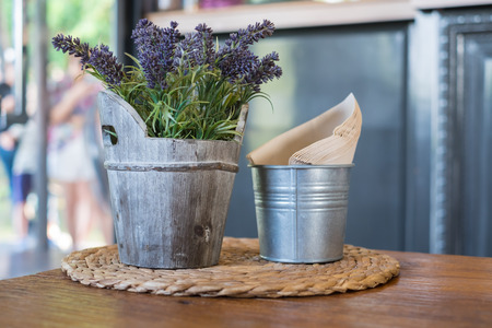 faked: Faked flowers in wooden bucket and napkin paper in bucket.