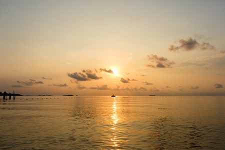 samet: Seascape of sea during sunrise with silhouette of small boat at Ao Lung Dam beach in Samet island, Thailand.