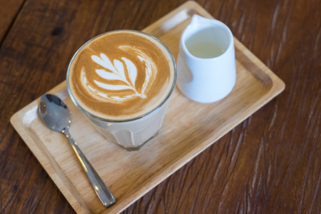the daily grind: Hot Piccolo latte coffee serve with syrup in wood tray on wooden table.