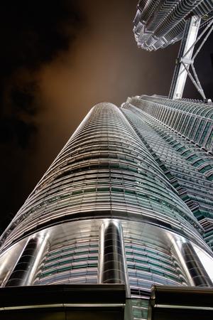 KUALA LUMPUR, MALAYSIA - FEBRUARY 29: Bottom view of Petronas twin towers at night on February 29, 2016 in Kuala Lumpur, Malaysia. Night scene of famous skyscraper.