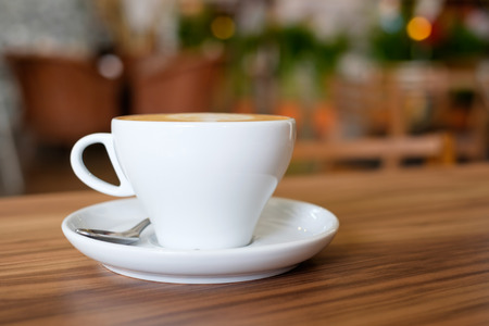 the daily grind: A white mug cup containing hot coffee on wooden table in cafe. Stock Photo