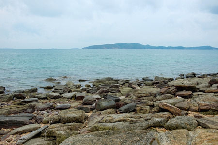 samet: Rocks on shoreline with sea and mountain background at Khao Laem Ya, Mu Ko Samet National Park in Thailand. Stock Photo