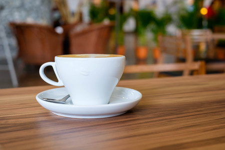 the daily grind: White mug cup of hot coffee on wooden table in coffee shop.
