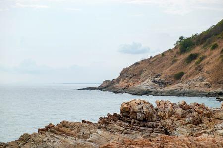 Rock cliff with view of the sea coastline at Khao Laem Ya, Mu Ko Samet National Park in Thailand.