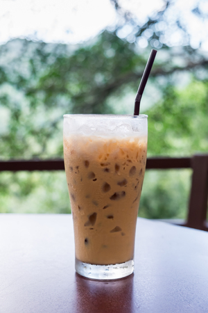 the daily grind: A glass of iced coffee on table in coffee shop with natural background.