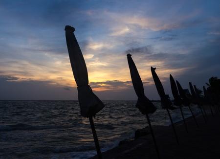 Silhouette beach umbrella at bangsan in Thailand Stock Photo