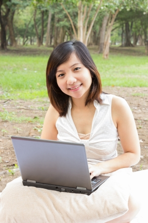 Asian woman smiling with laptop sitting at park Stock Photo