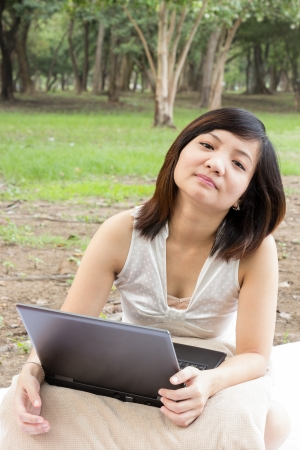 Asian woman flagging with laptop sitting at park Stock Photo - 16505489