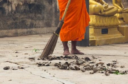 Monk sweeping leaf