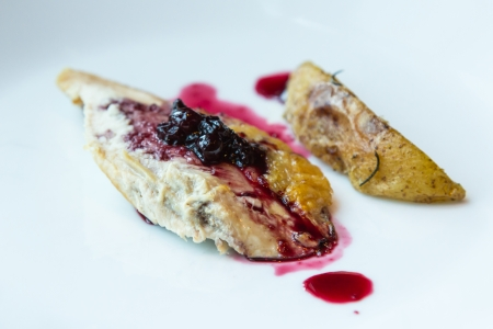 Roast chicken with blueberry sauce on white plate