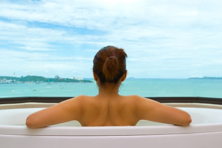 Backside woman in bathtub on sea view photo