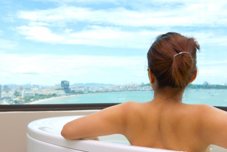 Backside woman in bathtub looking sea view  photo