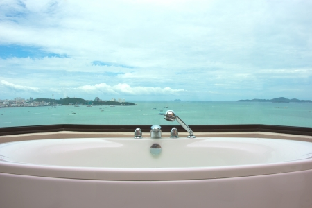 Bathtub in restroom on sea view background  photo