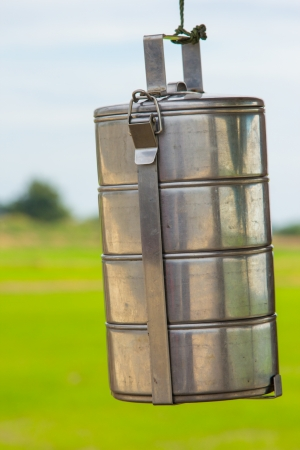 tiffin: Closeup tiffin carrier on green field background Stock Photo