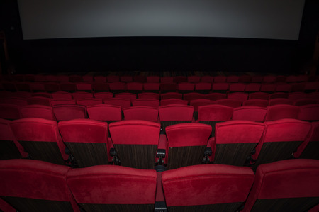 Empty comfortable red seats in thearter back side to screen  Stock Photo