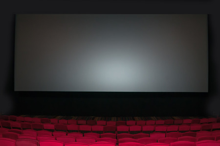 Empty seat on row in thearter with movie screen