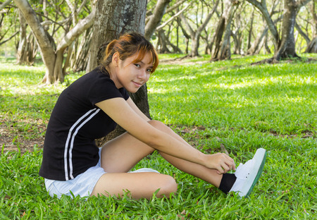 Young women sitting with lacing on sneaker  photo
