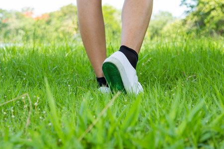 Foot in sneaker with step on foreground grassland