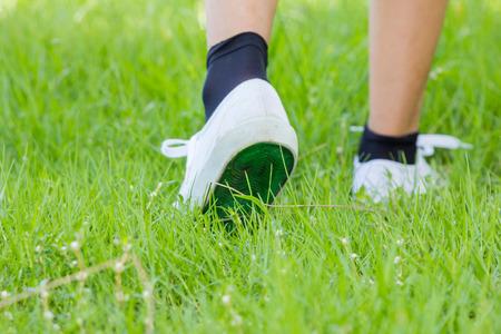 Foot in sneaker walking on grassland  Stock Photo
