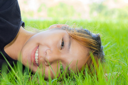 Portrait young women horizontal on grass with her face closeup  Stock Photo