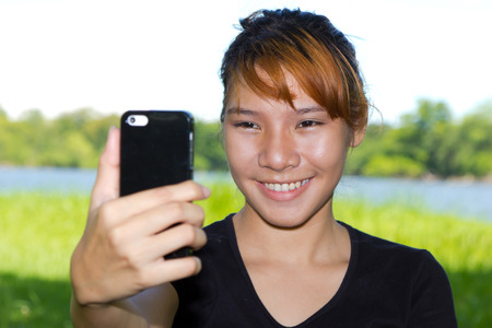 Asian women taking pictures of themselves with a cellphone Stock Photo