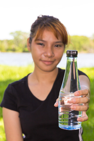 Young women with hold the bottle of drinking water